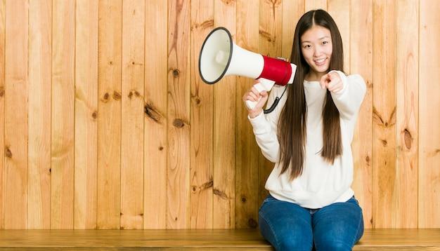 Giovane donna asiatica che tiene i sorrisi allegri di un megafono che indicano la parte anteriore.