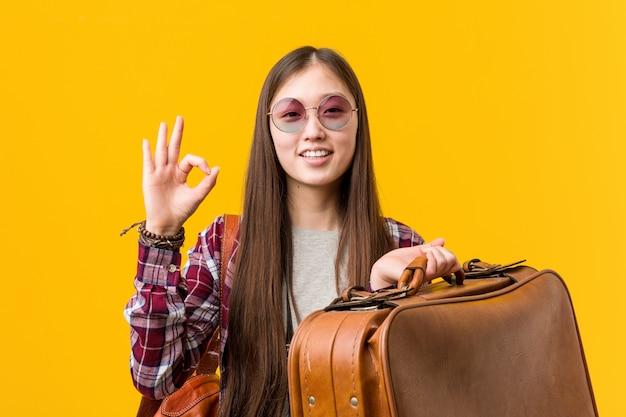 Giovane donna asiatica che tiene un gesto giusto di mostra allegro e sicuro di valigia.