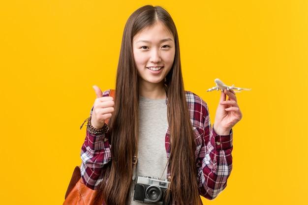 Giovane donna asiatica che tiene un'icona dell'aeroplano che sorride e che alza pollice in su