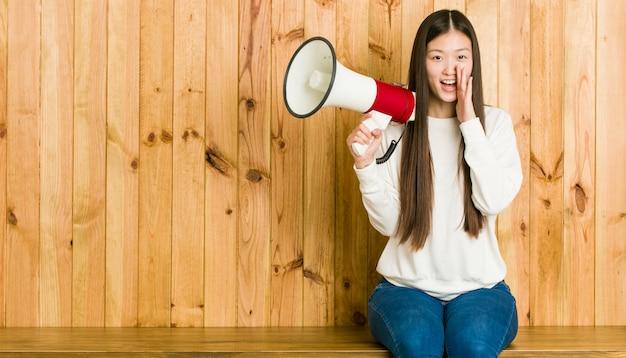 Giovane donna asiatica che tiene un megafono che grida eccitato alla parte anteriore.