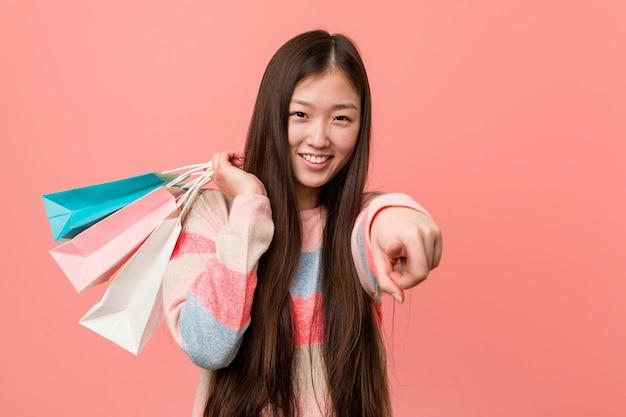 Giovane donna asiatica che tiene un sorriso allegro del sacchetto della spesa che indica la parte anteriore.