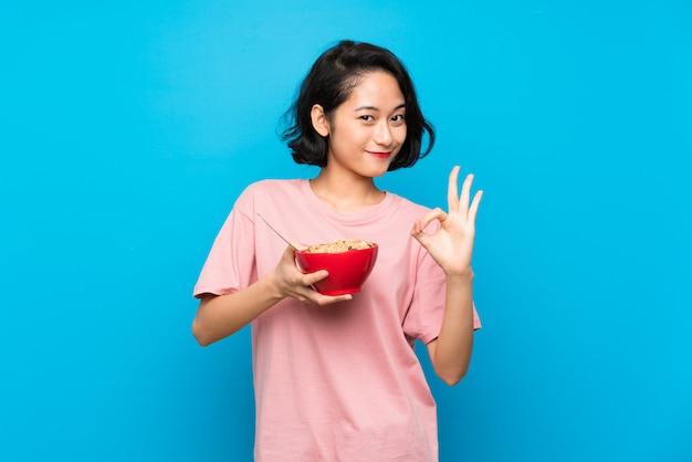 Giovane donna asiatica che tiene una ciotola di cereali che mostra segno giusto con le dita