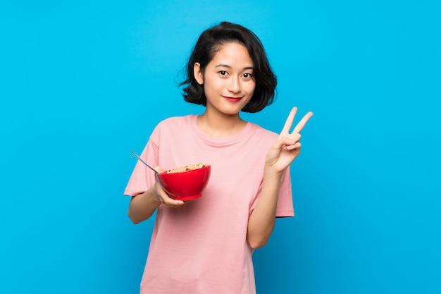 Giovane donna asiatica che tiene una ciotola di cereali che sorride e che mostra il segno di vittoria