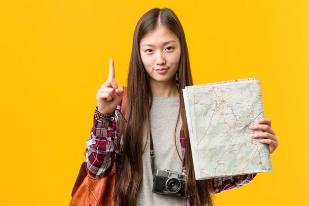 Giovane donna asiatica che tiene una mappa che mostra numero uno con il dito.