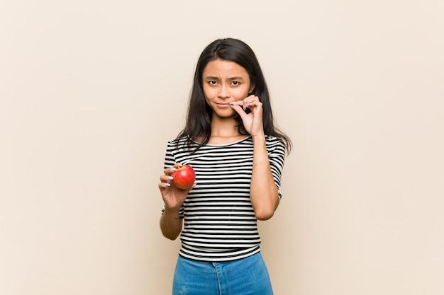 Giovane donna asiatica che tiene una mela con le dita sulle labbra che tengono un segreto.
