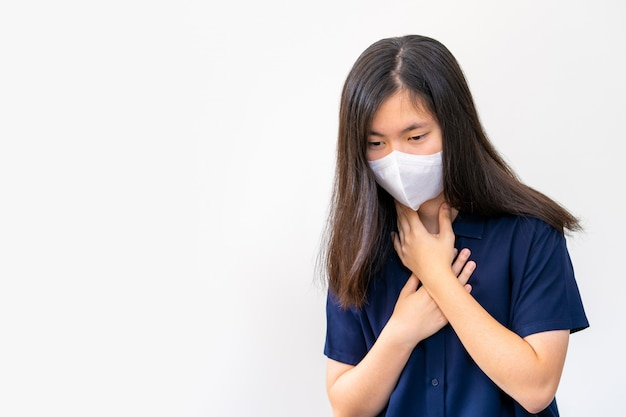Giovane donna asiatica che tossisce mentre indossa la maschera n95