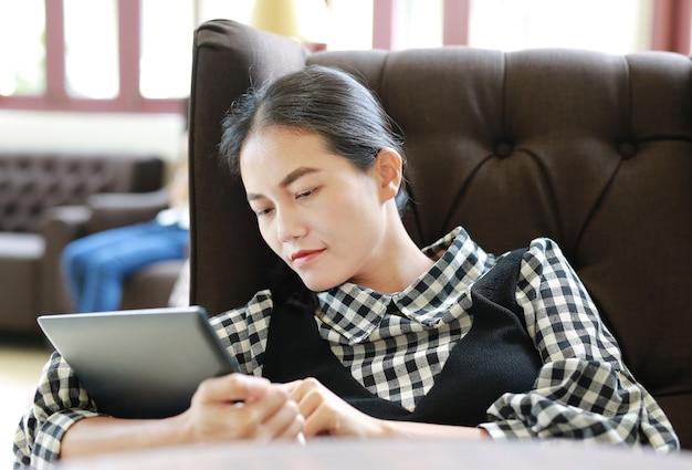Giovane donna asiatica che utilizza compressa nella biblioteca.