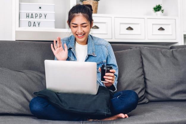 Giovane donna asiatica che utilizza computer portatile a casa