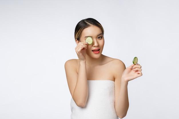 Giovane donna asiatica con fetta di cetriolo nelle sue mani isolato su sfondo bianco.