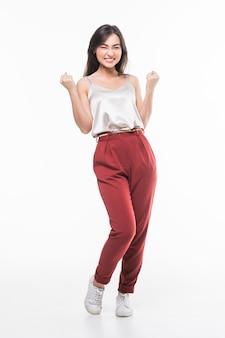 Giovane donna asiatica con gestere di conquista isolato sulla parete bianca