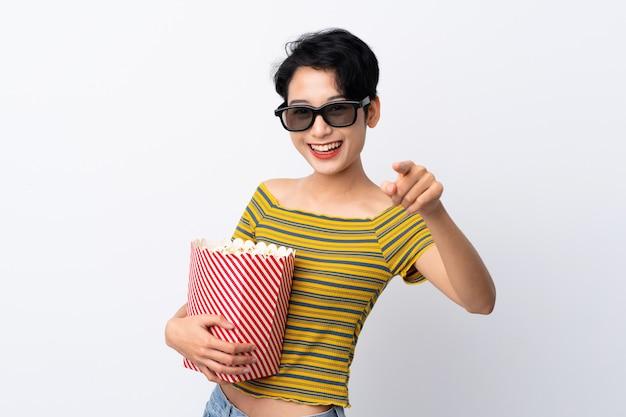 Giovane donna asiatica con gli occhiali 3d e in possesso di un grande secchio di popcorn mentre punta davanti