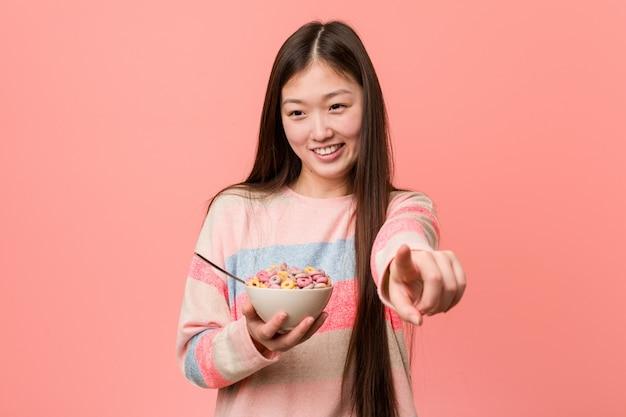 Giovane donna asiatica con i sorrisi allegri di una ciotola di cereale che indicano la parte anteriore.