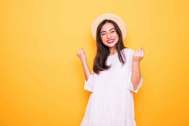 Giovane donna asiatica con il gesto di conquista isolato sulla parete gialla