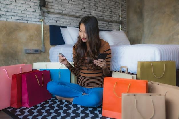 Giovane donna asiatica con il telefono cellulare e il computer portatile astuti facendo uso della carta di credito per la compera online
