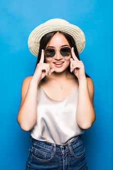 Giovane donna asiatica con la posa di sorpresa isolata su fondo blu. ritratto di bella donna asiatica in cappello di paglia e occhiali da sole su sfondo blu