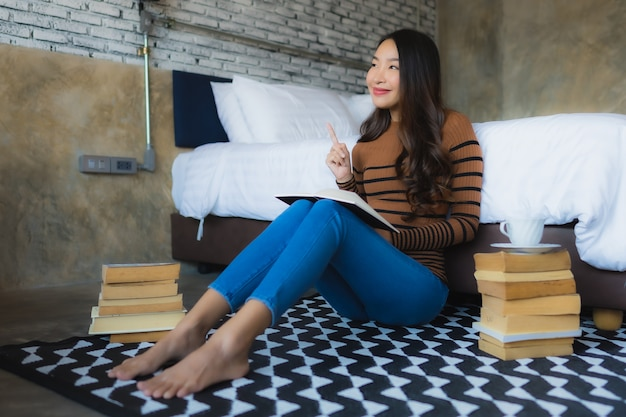 Giovane donna asiatica con la tazza di caffè e il libro letto