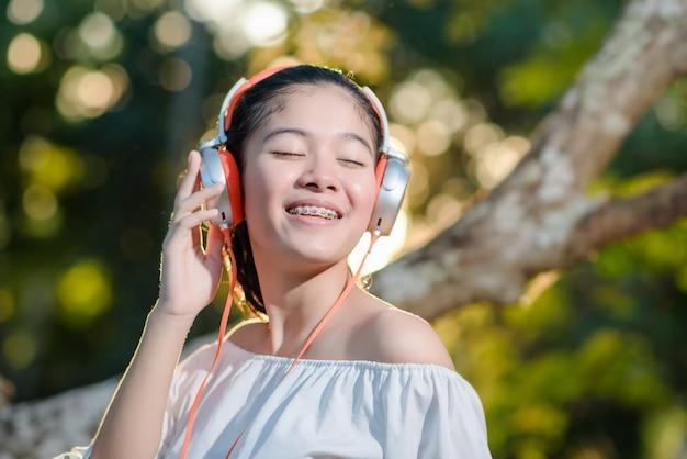 Giovane donna asiatica con le cuffie e la musica d'ascolto sul tramonto nel parco.