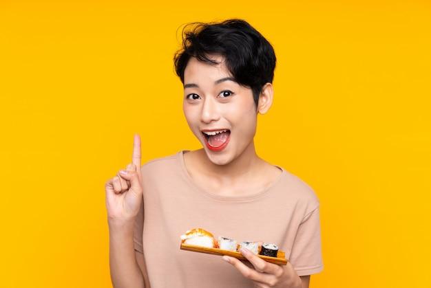 Giovane donna asiatica con sushi che indica una grande idea