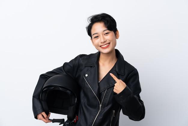 Giovane donna asiatica con un casco da motociclista con espressione facciale a sorpresa