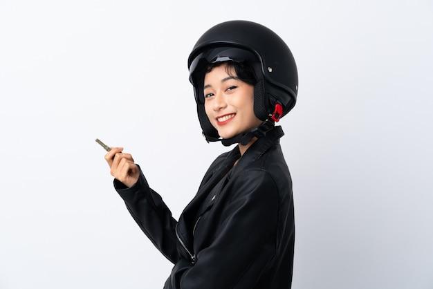 Giovane donna asiatica con un casco da motociclista e una chiave