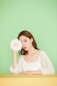 Giovane donna asiatica con un fiore dalia