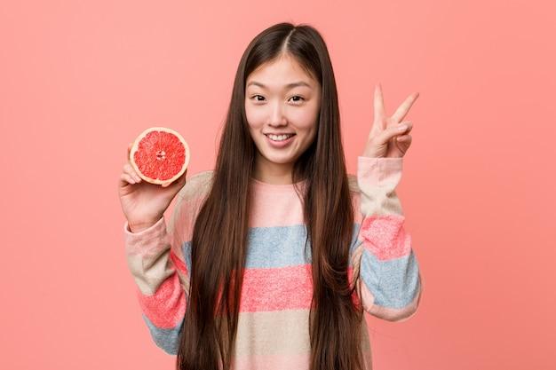 Giovane donna asiatica con un pompelmo che mostra il segno di vittoria e che sorride ampiamente.