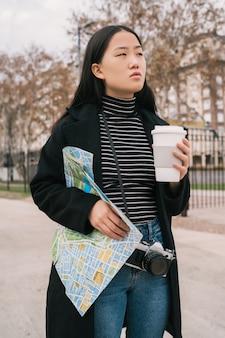 Giovane donna asiatica con una mappa.