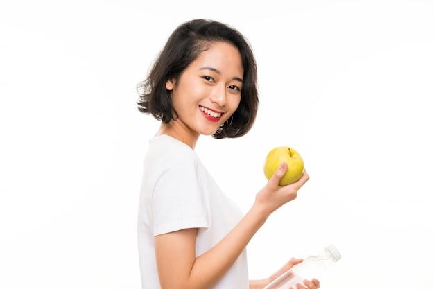 Giovane donna asiatica con una mela e una bottiglia di acqua