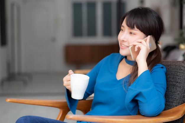 Giovane donna asiatica del bello ritratto che sorride facendo uso dello smart phone mobile
