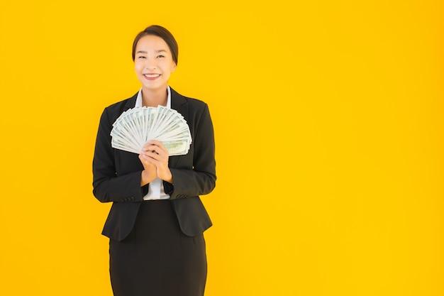 Giovane donna asiatica del bello ritratto con molti contanti dei soldi