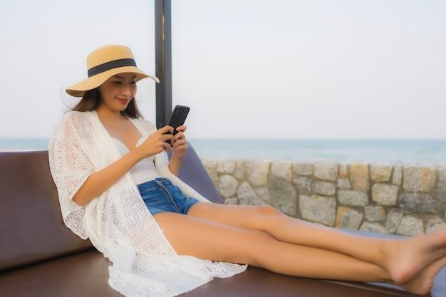 Giovane donna asiatica del ritratto che per mezzo del telefono cellulare astuto intorno al mare all'aperto della spiaggia