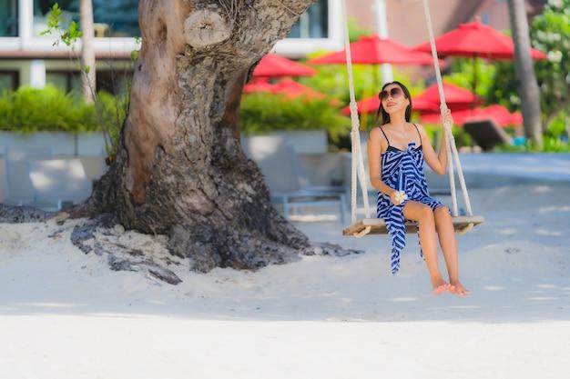 Giovane donna asiatica del ritratto che si siede sulla corda e sul mare dell'oscillazione intorno all'albero del cocco dell'oceano del mare della spiaggia