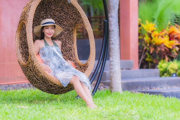 Giovane donna asiatica del ritratto che si siede sulla sedia dell'oscillazione nel giardino
