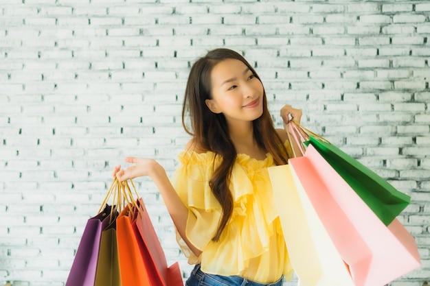 Giovane donna asiatica del ritratto che tiene il sacchetto della spesa variopinto