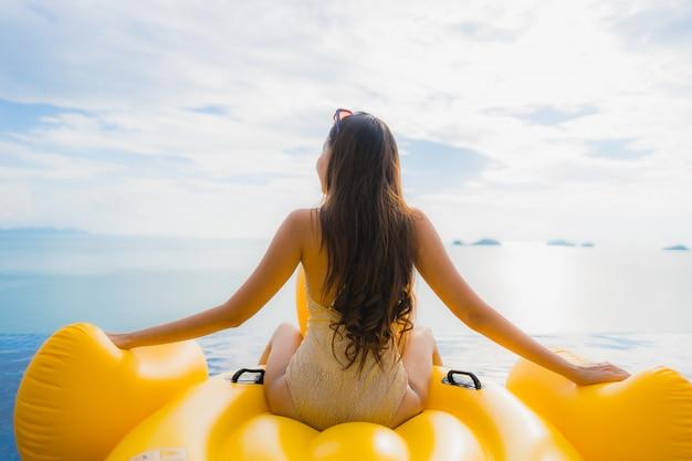 Giovane donna asiatica del ritratto sull'anatra gonfiabile di giallo del galleggiante intorno alla piscina all'aperto in hotel e ricorso
