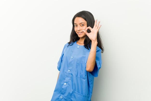 Giovane donna asiatica dell'infermiera allegra e sicura che mostra gesto giusto.