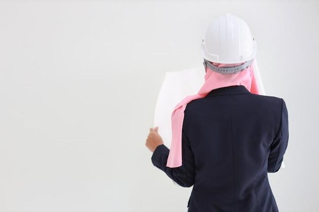 Giovane donna asiatica dell'ingegnere musulmano attivo e astuto nel modello sicuro sorridente della tenuta del vestito blu