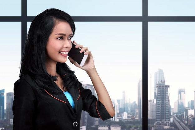 Giovane donna asiatica di affari che per mezzo del telefono cellulare