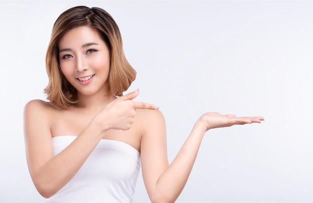 Giovane donna asiatica di bellezza che indica mano per il prodotto su fondo bianco