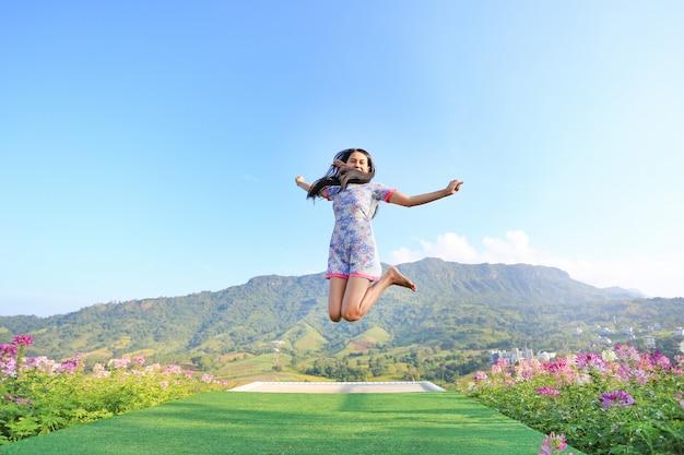 Giovane donna asiatica di salto che si sente libero con le armi spalancate ai bei alberi e montagne su cielo blu.