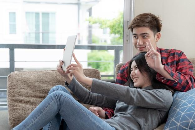 Giovane donna asiatica e uomo bello che si siedono sullo strato facendo uso del dispositivo