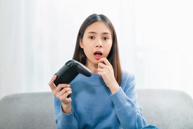 Giovane donna asiatica emozionante che si siede sul sofà