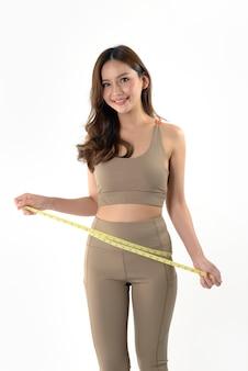 Giovane donna asiatica esile che misura del suo corpo