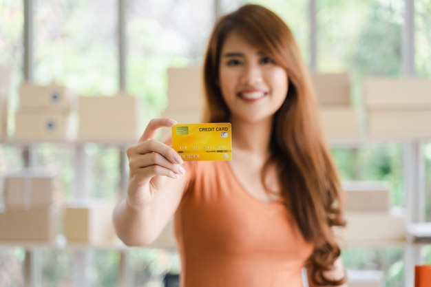 Giovane donna asiatica felice attraente che mostra la carta di credito a disposizione