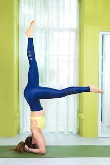 Giovane donna asiatica felice attraente che si esercita nel suo equilibrio di yoga, supporto della testa, a casa studio