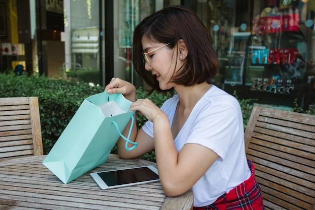 Giovane donna asiatica felice che compera un mercato all'aperto con fondo delle costruzioni e del cielo blu pastelli