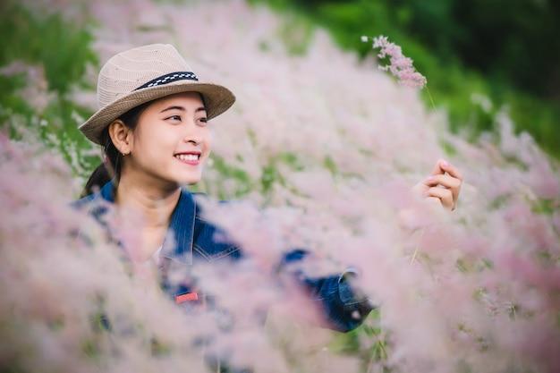 Giovane donna asiatica felice che si siede sul campo di erba