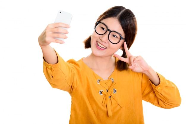 Giovane donna asiatica felice che sorride mentre prende la foto del selfie con il telefono cellulare e dà il segno di pace