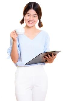 Giovane donna asiatica felice che sorride mentre tiene appunti e tazza di caffè