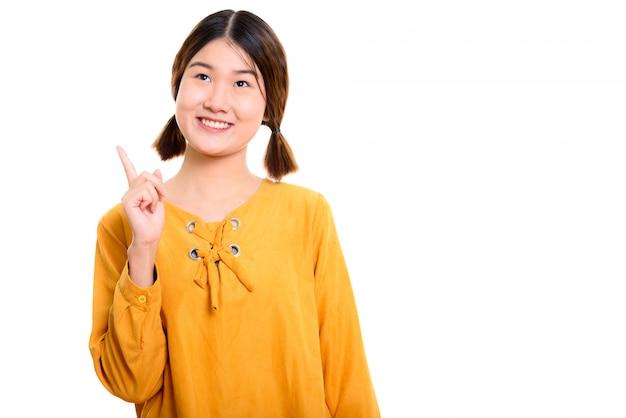 Giovane donna asiatica felice premurosa che sorride mentre punta il dito verso l'alto